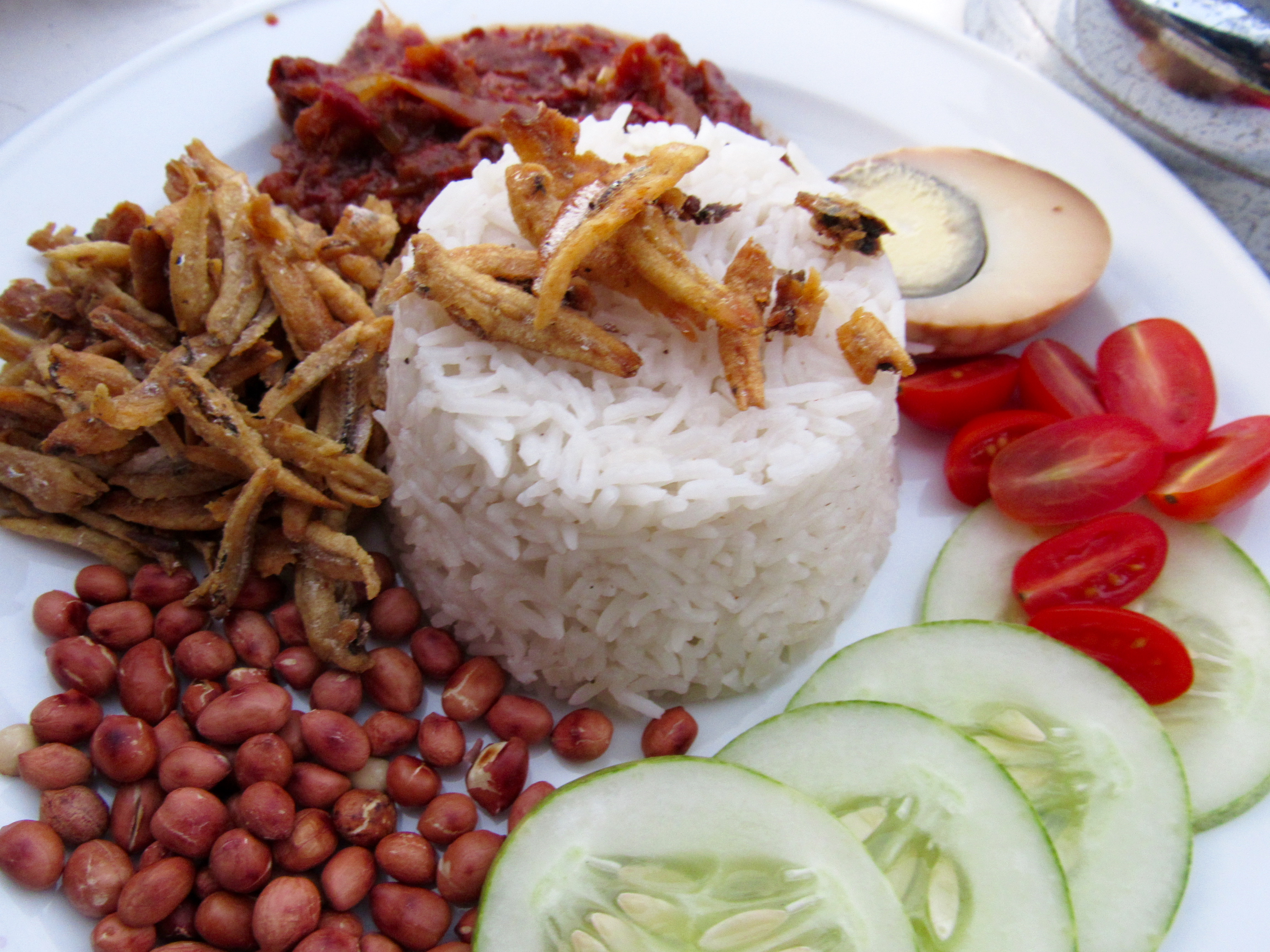 with egg, dried fish, coconut rice, cucumber and tomato and the nasi lemak sauce