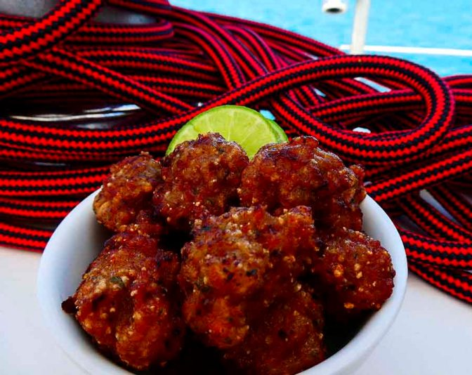 Larb Moo Tod - Fried Pork Balls Thai style. Displayed in a white bowl. They are being served on a boat and the background has the headsail furler rope in it.