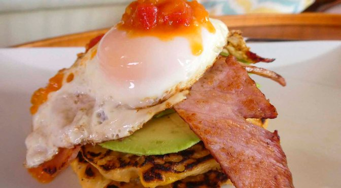 Corn fritters with avocado, bacon, egg and warm tomato relish